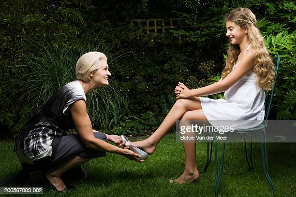 Grandma putting silver shoe on granddaughter's (10-11) foot in garden
