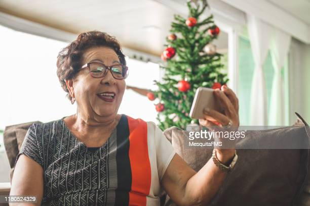 grandma receiving christmas message by smart phone - grandmother stock pictures, royalty-free photos & images