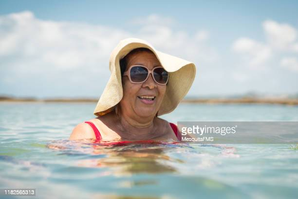 grandma swimming on the tropical beach - uv protection stock pictures, royalty-free photos & images