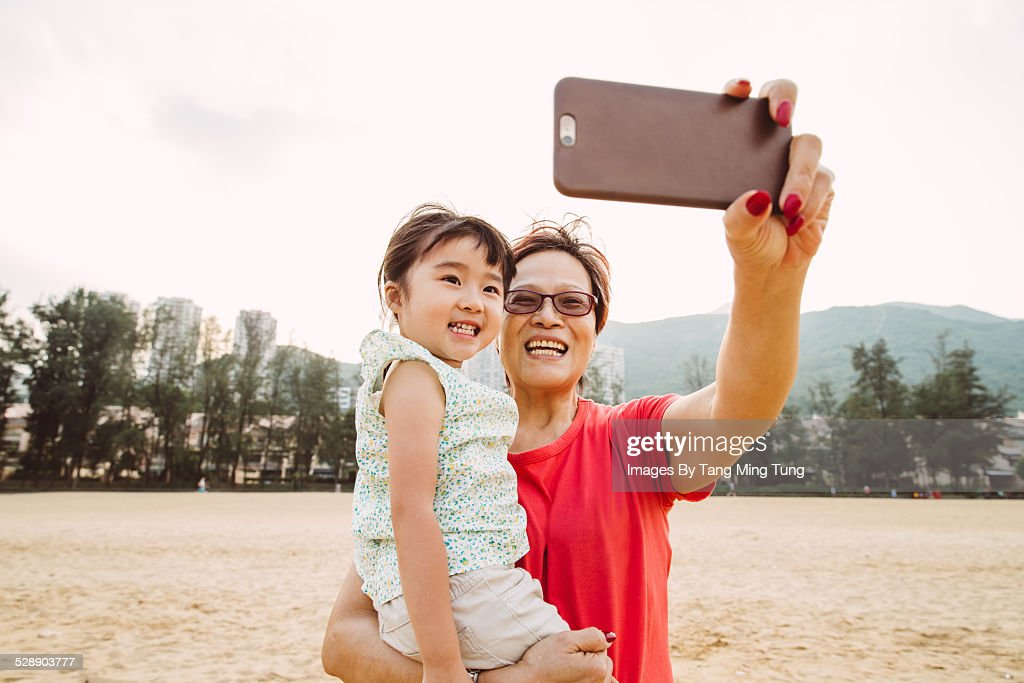 Grandma carrying lovely little girl while taking selfies with her together with a smartphone joyfully on the beach.