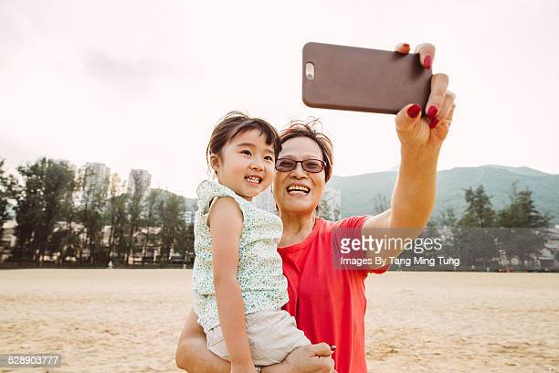 Grandma taking selfies with toddler on beach