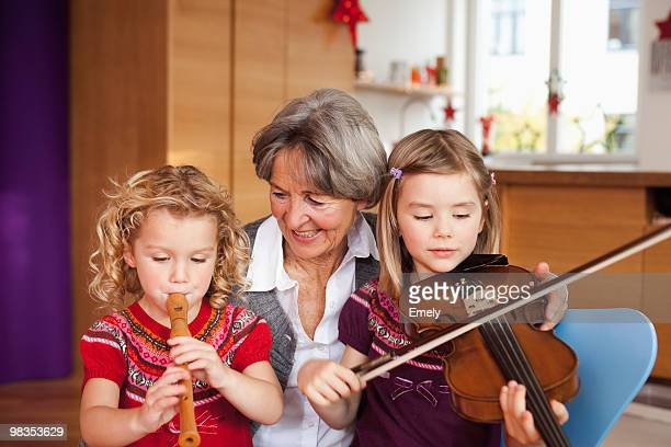 grandma teaching grandchildren music - recorder musical instrument stock photos and pictures