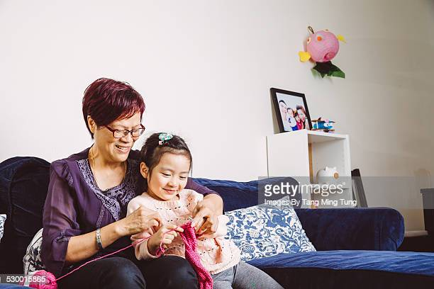 Grandma teaching little grand daughter to knit