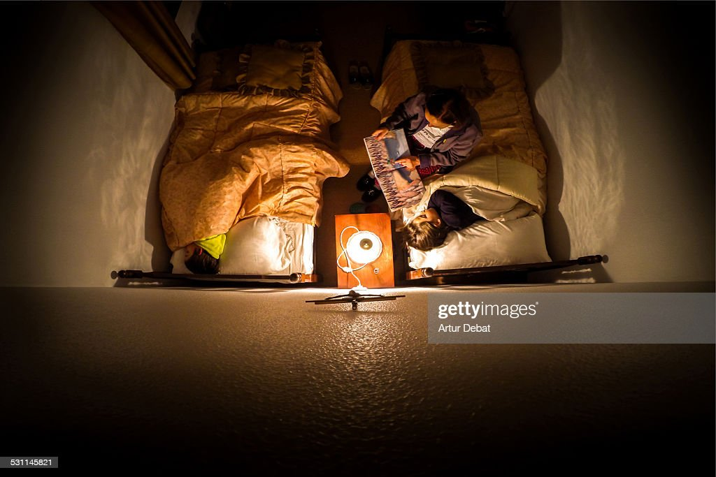 Grandma telling a night tale to grandsons at home. : Stock Photo