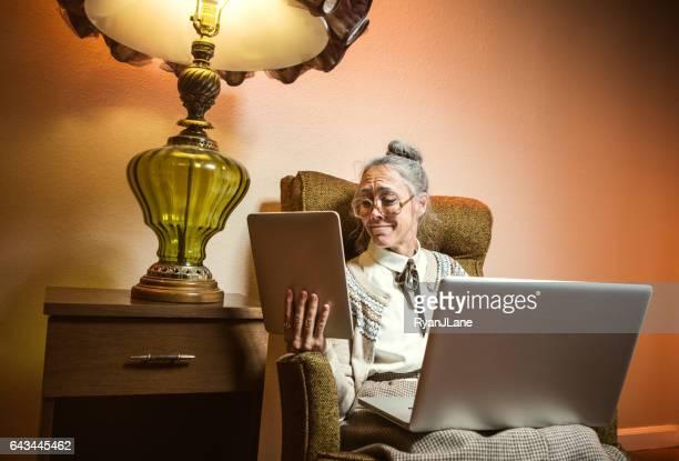 Grandma Using Multiple Modern Electronics