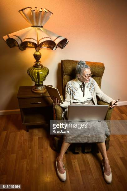 grandma using multiple modern electronics - rocking chair stock photos and pictures