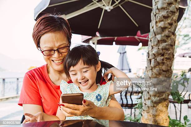 Grandma using smartphone with todller in cafe