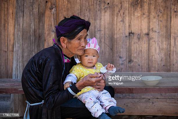 CONTENT] grandmonther feeding the leftbehind baby whose parents are outmigrantion for work at Xiaohuang Dong villageGuizhou province