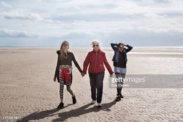 grandmother and adolescent grandchildren walking along a beach in england on a cold, windy day - lancashire stock pictures, royalty-free photos & images