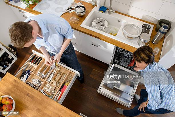 Grandmother and adult grandson tidying away cutlery from dishwasher