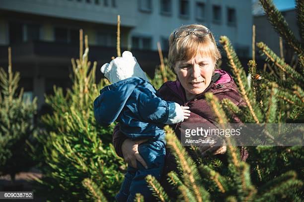 Grandmother and baby choosing christmas tree