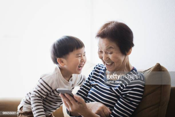 grandmother and boy using  a smart phone together at home - asia stock pictures, royalty-free photos & images