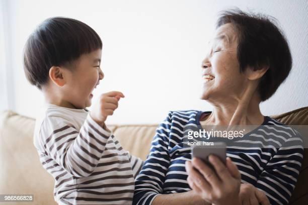 祖母と家で一緒にスマート フォンを使用して少年 - 80代 ストックフォトと画像