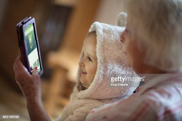 Grandmother and child looking at a portable information device together