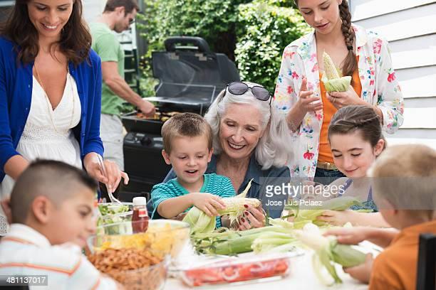 Grandmother and children husking corn