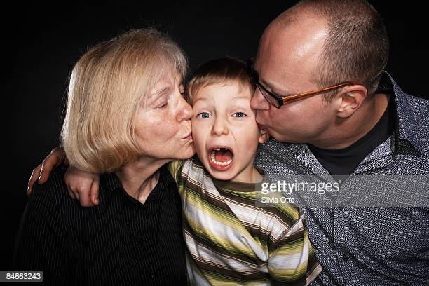 grandmother and dad kissing  and son - femme entre deux hommes photos et images de collection
