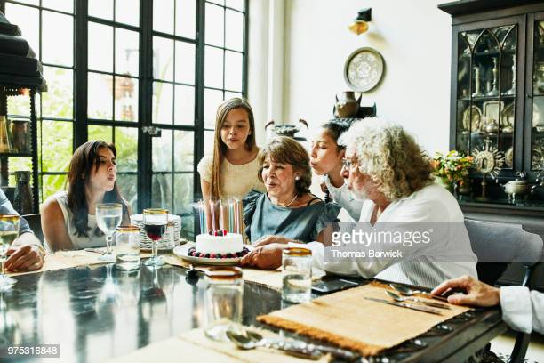 Grandmother and family blowing out candles on birthday cake during dinner party