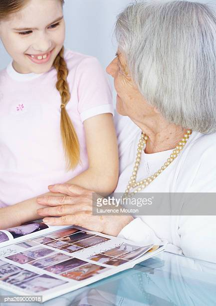 Grandmother and girl looking at comic book