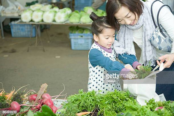 Grandmother and girl putting vegetable in bag