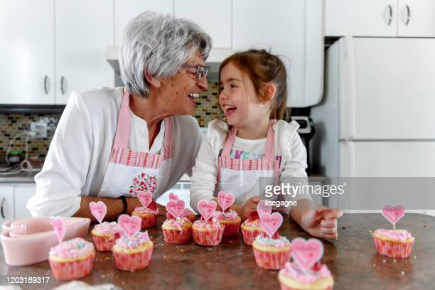grandmother and grandchild cooking - valentine's day stock pictures, royalty-free photos & images