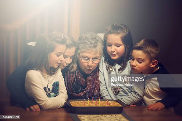 grandmother and grandchildren blowing out candles