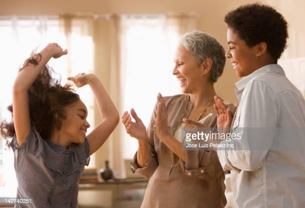 Grandmother and grandchildren dancing together