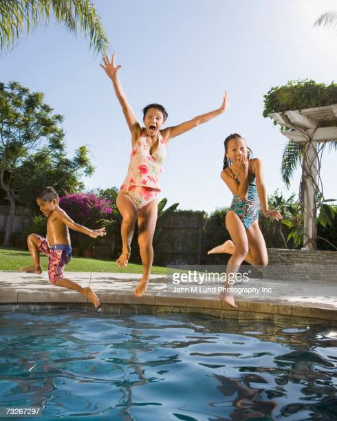 Grandmother and grandchildren jumping into swimming pool