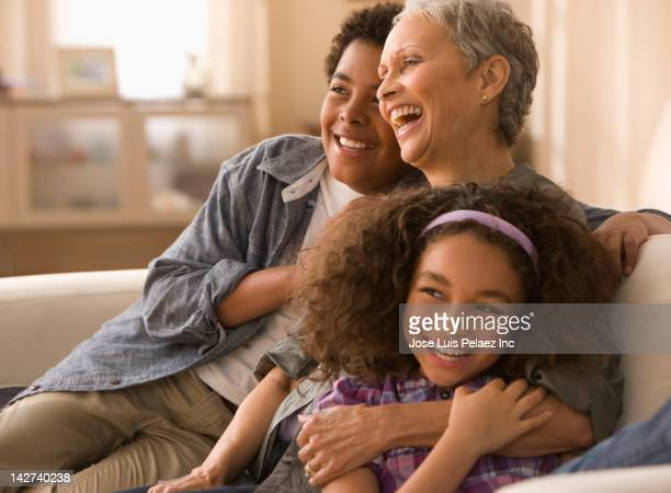 grandmother and grandchildren laughing on sofa - generation gap stock pictures, royalty-free photos & images