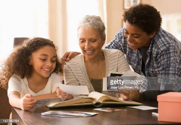 grandmother and grandchildren looking at photographs - childhood photo album stock photos and pictures