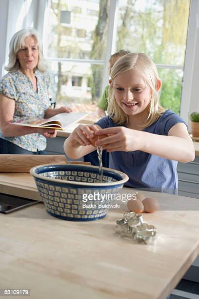 Grandmother and grandchildren (6-9) preparing food in kitchen