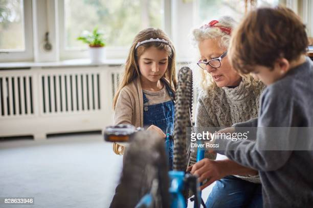 Grandmother and grandchildren repairing bicycle at home