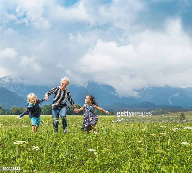 Grandmother and grandchildren running in field holding hands, Fuessen, Bavaria, Germany
