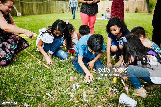grandmother and grandchildren trying to gather candy from broken pinata during birthday party - pinata stock pictures, royalty-free photos & images