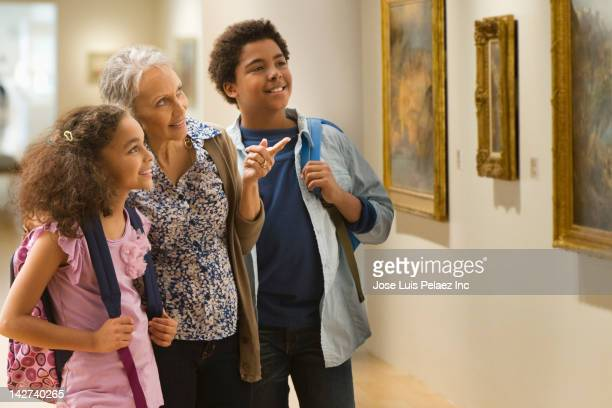 grandmother and grandchildren visiting a museum - museum stock pictures, royalty-free photos & images