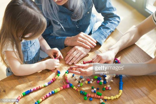grandmother and granddaughter and mother threading beads - bead stock pictures, royalty-free photos & images