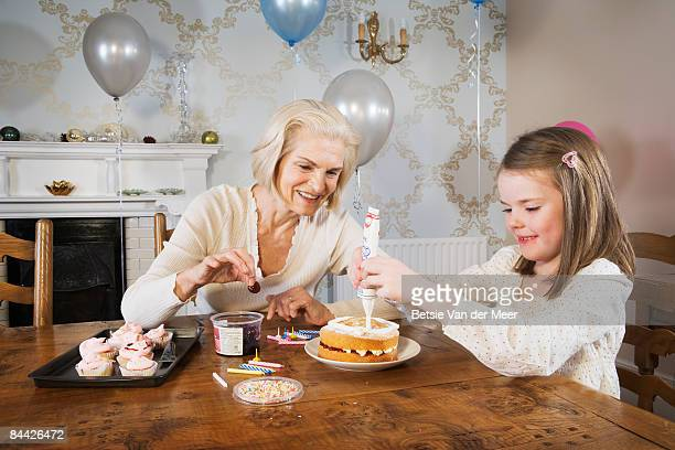 Grandmother and granddaughter are decorating cake.
