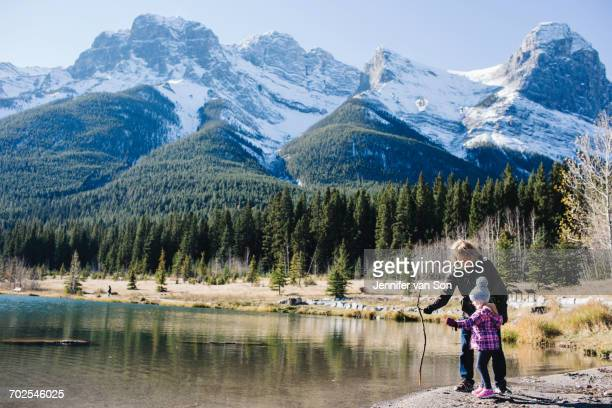 Grandmother and granddaughter beside river, Three Sisters, Rocky Mountains, Canmore, Alberta, Canada
