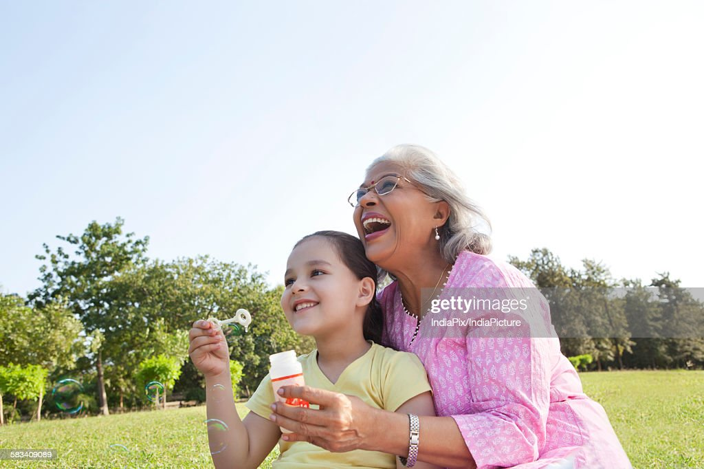 Grandmother and granddaughter blowing bubbles : Stock Photo