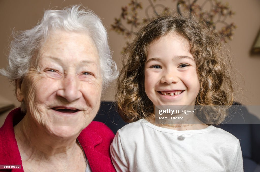 Grandmother and granddaughter both showing lack of teeth by smiling : Stock Photo