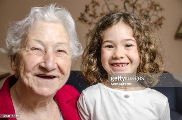 Grandmother and granddaughter both showing lack of teeth by smiling