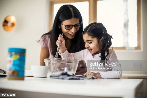 Grandmother and granddaughter cooking at home