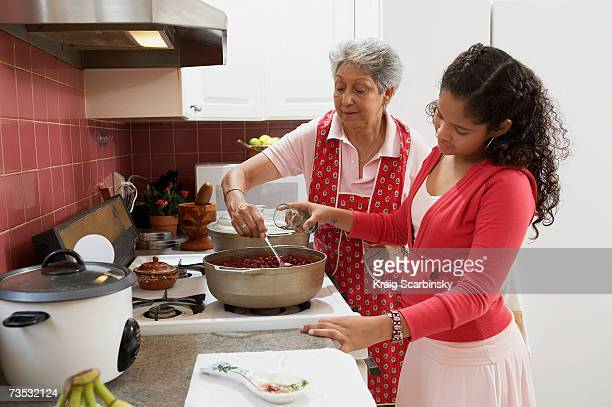 Grandmother and granddaughter (10-12) cooking in kitchen