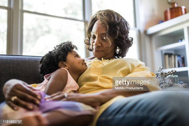 grandmother and granddaughter cuddling on couch - grandmother stock pictures, royalty-free photos & images