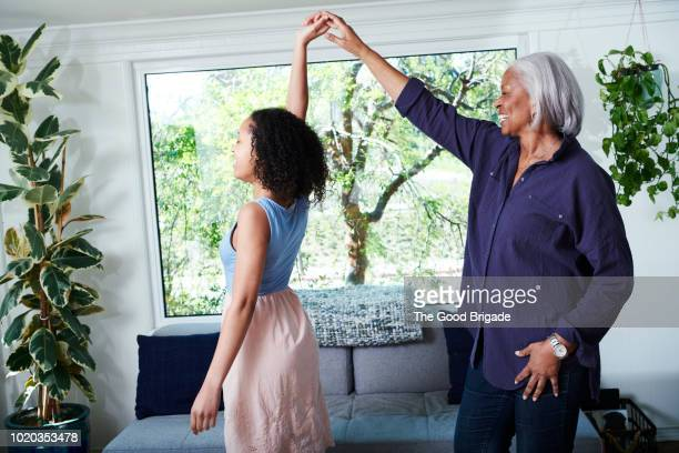 grandmother and granddaughter dancing in living room at home - images of black families stock pictures, royalty-free photos & images