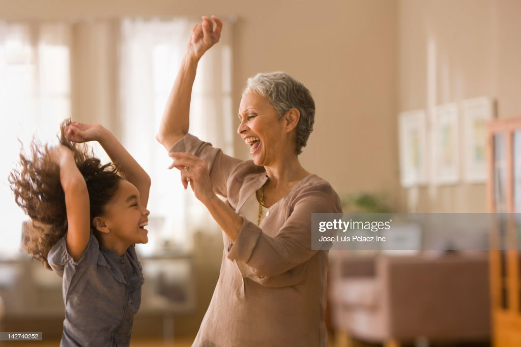 Grandmother and granddaughter dancing together : Stock Photo