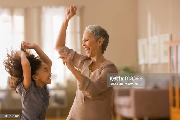grandmother and granddaughter dancing together - african american family home stock photos and pictures