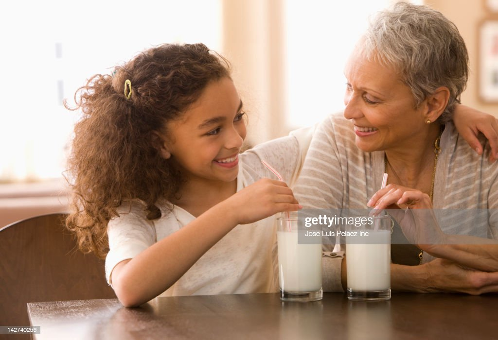 Grandmother and granddaughter drinking milk : Stock Photo