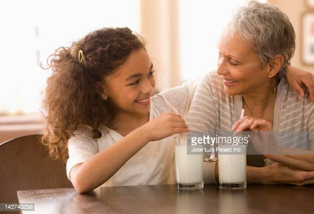 Grandmother and granddaughter drinking milk