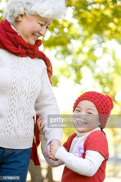 Grandmother and Granddaughter Enjoying a Park in Autumn