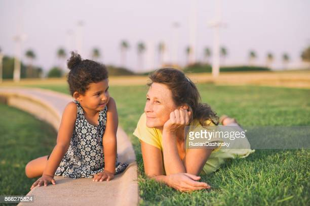 Grandmother and granddaughter enjoying outdoors on the grass.